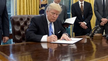 U.S. Donald Trump signing a document. The budget will fund research into gun violence for the first time in years.