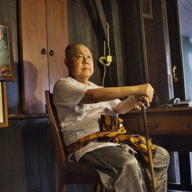 Sulak Sivaraksa, who has been charged or arrested five times under Thailand's lese-majeste law, at home in Bangkok. To the left is a photo of Sulak with the late king, Bhumibol Adulyadej.