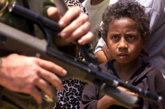 An East Timorese child stares at a passing Australian soldier as peacekeepers and UN officials visited a refugee camp in Dare, East Timor, 21 September 1999.