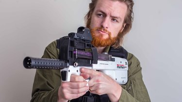 Toy shop owner Brad Towner with one of his gel gun blasters