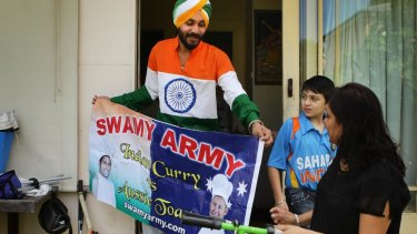 """Gurnam Singh shows his sister Manjeet Bailie and nephew Rajeer Singh the banner he made for the """"Swami army""""."""