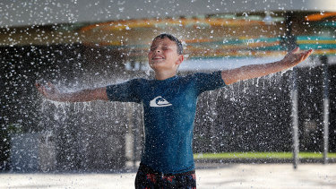 Hudson Battersby, 11, from Brassall, plays under the water curtain at Tulmur Place in Ipswich's Nicholas Street Precinct.