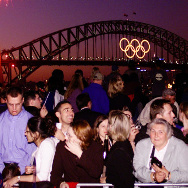 Crowds at the Sydney Opera House watch the Olympic Rings light up the Sydney Harbour Bridge.