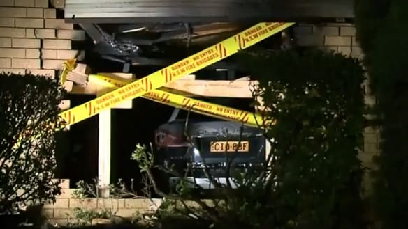 Car crashes into Sydney home and bursts into flames