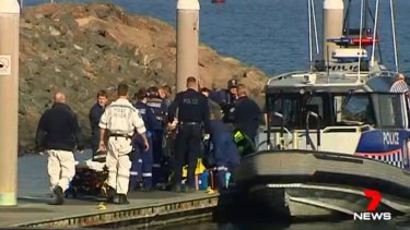 Emergency services attempt to rescue rock fisherman at Cape Banks.