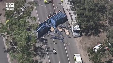 Henry Lawson Drive is closed in both directions at Milperra following a crash involving two trucks and a car.