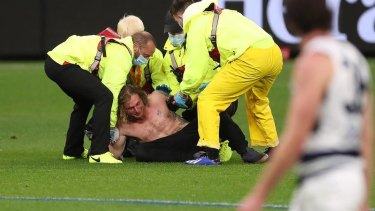 Topless and now jobless: Optus Stadium security subdue pitch invader Jesse Hayen, who was fined $8000 in a Perth court on Friday.