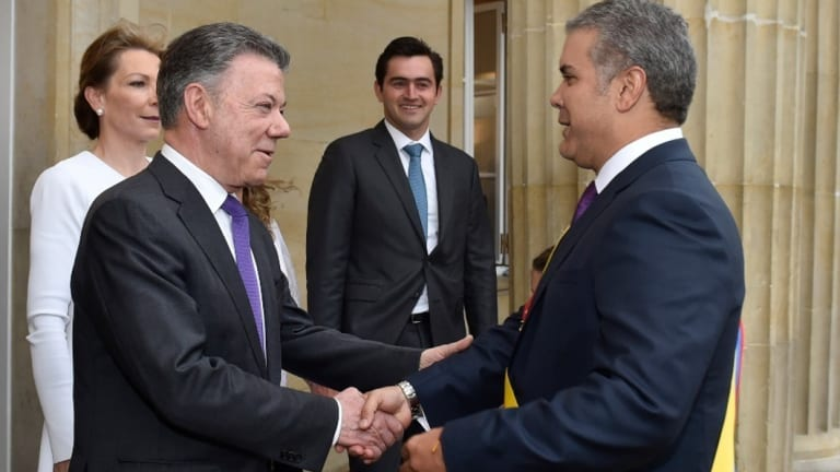 Colombia's outgoing President Juan Manuel Santos, left, welcomes newly sworn-in President Ivan Duque in Bogota,
