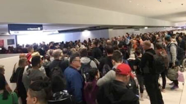 Hundreds of people stand in line at international departures gate because of smoke in the screening area.