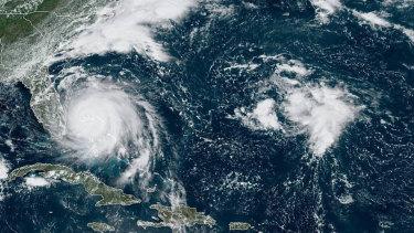 Hurricane Dorian, left, churning over the Bahamas.