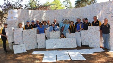 Rotary District 9710 members with the massive 90th birthday card signed by11,515 people at its Floriade marquee.