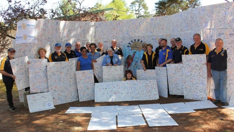 Rotary District 9710 members with the massive 90th birthday card signed by 11,515 people at its Floriade marquee.