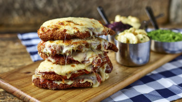 Meet the Schnitzelmeister. It's a six-stack, chicken schnitzel tower topped with Napoli sauce, ham and cheese and served with four side dishes.