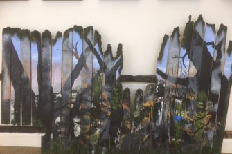 Images from a burnt fence are part of the art exhibition in Mallacoota, a year after the fires.
