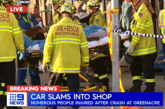 Emergency workers remove victims from a shop after a car slammed into Hijab House in Greenacre in Sydney's south-weston Thursday.