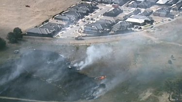 The grassfire is burning close to homes.