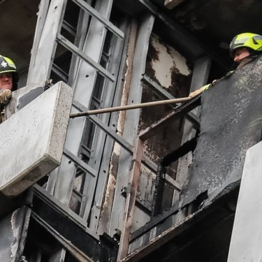 Firefighters survey the damage on the Neo 200 tower block in Melbourne's Spencer Street.