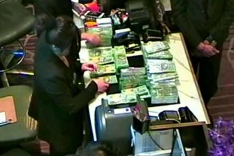 A large amount of cash being exchanged at Suncity's privategaming room at Crown Melbourne.