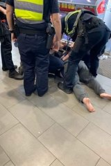A photo of Carol being handcuffed by police.