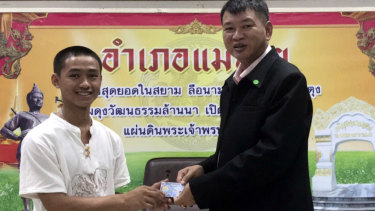 "Adul ""Dul"" Sam-on, 14, left, receives his Thai identity card on Wednesday."