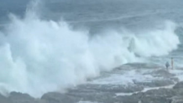 The large wave crashed onto rocks where the couple was walking, pulling them into the sea.