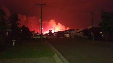 Emergency crews battle a bushfire near homes at Belmont on Thursday night.