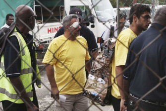 Two injured asylum seekers leave Manus Island following riots at the detention centre.