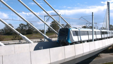 A driverless metro train passes over the new cable-stayed bridge at Rouse Hill for the first time.