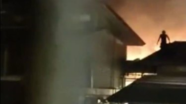 Footage posted on social media shows a Christmas Island detainee jumping on the roof of a compound on Tuesday night, with a fire in the background.