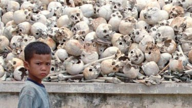 A Cambodian boy stands in front of  human skulls discovered 25 km south of Phnom Penh in 1995. The mass grave contains the remains of about 2000 victims of the Khmer Rouge.