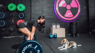 "Sophie Forkgen, 32, gets her ""puppy fix"" working out at the newly opened dog-friendly gym."