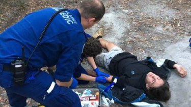 Paramedics attend to Darcy McKay after his bike crashed on a rutted dirt track in Pambula Beach. He used Siri to call triple zero.