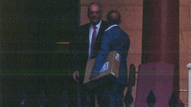 A surveillance photograph shows Joseph Alha, carrying a box with a building model, meeting Daryl Maguire at Parliament in 2017.