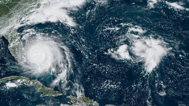 Hurricane Dorian, left, churning over the Bahamas.