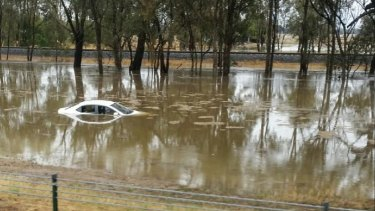 A car is mostly submerged in floodwater on the Hume Freeway.