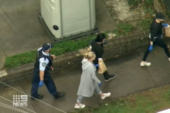 The woman is escorted by police, with her hands in evidence bags.