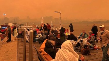 Locals and tourists on the Mallacoota wharf as fire devastated the region over summer.