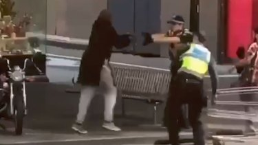 Police officers confront Hassan Khalif Shire Ali on Bourke Street.