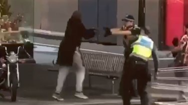 Police confront Shire Ali on Bourke Street on Friday.