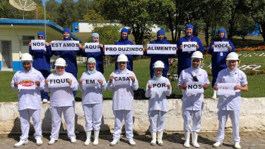 "JBS Brazil employees pose with signs saying ""We're here making food for you, stay home for us"". In a statement, the company said it was committed to production operations ""with great care to supply food in a time of need""."