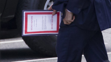 Outgoing acting US Defence Secretary Patrick Shanahan carries a document labelled secret as he arrives for a meeting with President Donald Trump about Iran at the White House on Thursday.