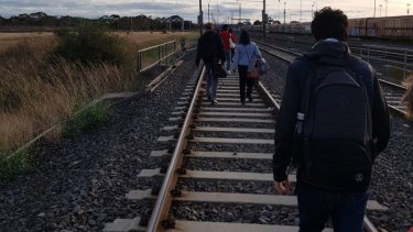 Passengers walk along the tracks after a train hit overhead cables