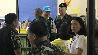 Rescue mission chief Narongsak Osottanakorn (in blue hat) embraces his colleagues.