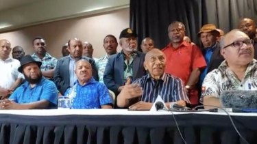PNG Prime Minister Peter O'Neill (right) announcing he would step aside on Sunday. Sir Julius Chan (centre right) was his nominated successor.
