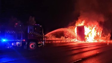 Firefighters work to extinguish a blaze that engulfed a Woolworths truck on the Hume Motorway.