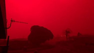After being shrouded in darkness, the sky at Mallacoota turns an eerie shade of red as fires bear down on Tuesday morning.
