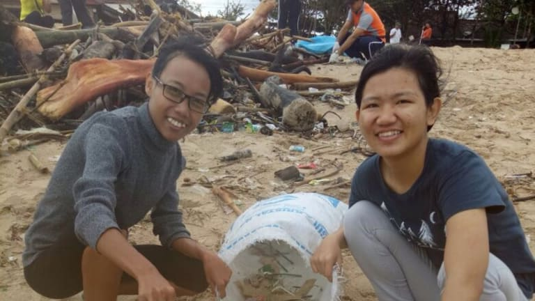 Bali Wise Program Co-ordinator Fena Evans (left) and a student take part in a beach clean-up run by the ROLE Foundation in Bali.