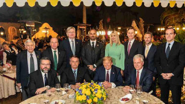US President Trump hosts a working dinner for Brazilian President Jair Bolsonaro, seated second from left, and his delegation. The Brazilian ambassador, Nestor Forster, standing behind Bolsonaro, has also tested positive for coronavirus.