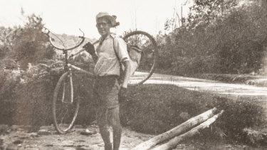 Alan McArthur carries his bike across a creek during the ride.