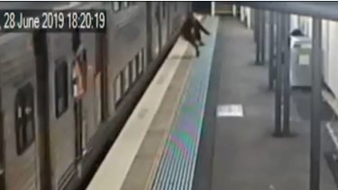 Camera footage shows a man jump from a moving train onto a station platform in June.